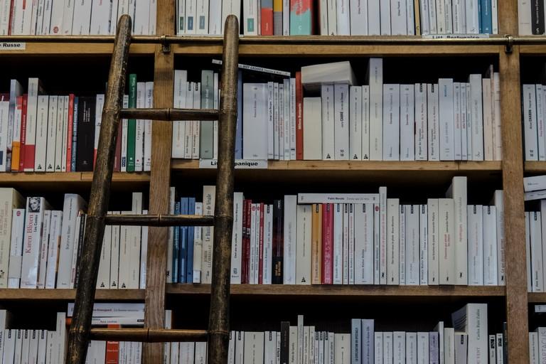 Scala di legno appoggiata a una libreria